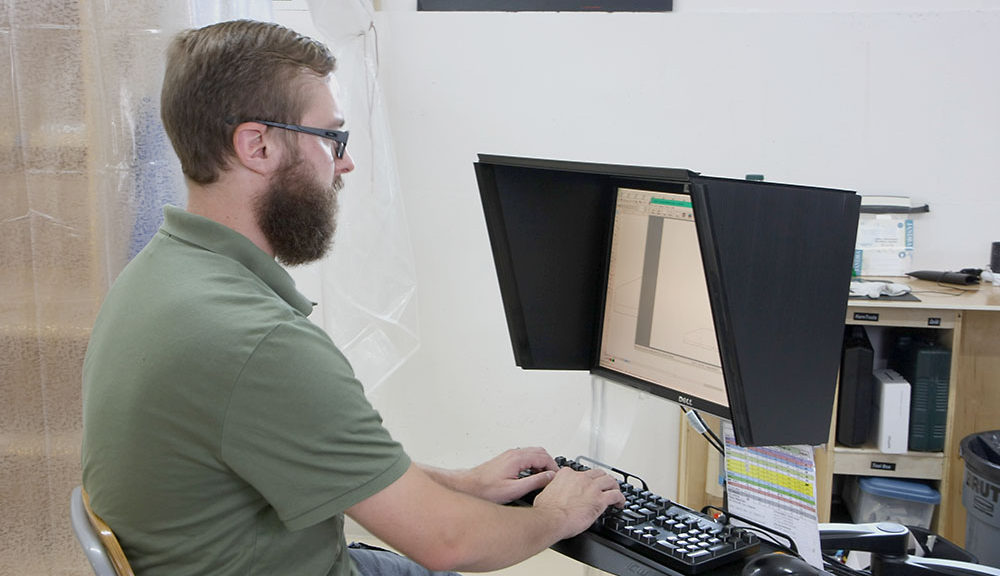 Man at a computer that has an indoor-outdoor monitor hood installed on it